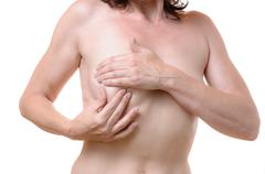 Middle-aged woman checking her breast for lumps - stock photo
