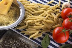 Pasta, tomatoes, garlic, basil and grated cheese. Stock Photos