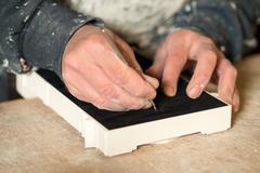 Hands Cutting Black Felt Paper on a Plaster Model Stock Photos