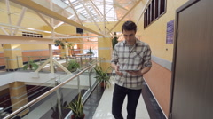Young man walks through shopping mall with tablet in his hands Stock Footage