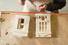 Overhead of Scale Model Buildings and Parts on Wooden Table Stock Photos