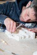 Male Sculptor Carving a Plaster Model - stock photo