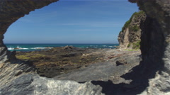 AERIAL: Flying through amazing rocky window overlooking stunning stony seashore Stock Footage
