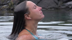 SLOW MOTION: Young woman in bikini raises form underwater to surface for air - stock footage