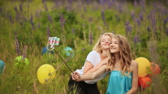 Two young pretty girls make selfie. Students are sitting on the lawn in the park Stock Footage
