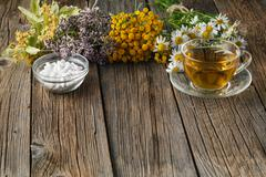 Healing herbs and bowl of pills on wooden table Stock Photos