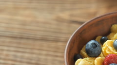Bowl of corn flakes and fresh berries on wooden background Stock Footage