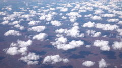 SLOW MOTION: View of arid landscape from airplane high above white clouds - stock footage