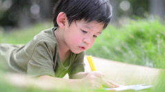 Cute Asian child drawing picture with crayon,outdoors Stock Footage