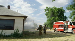 Pan of firemen next to smoking house - stock footage