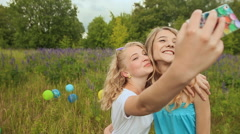 Two young blonde girls are photographed on the phone. Make selfie Stock Footage