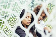 Young pretty multi ethnicity afro-american girls having fun on foothball field Stock Photos