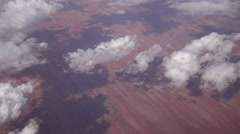 SLOW MOTION: View of red arid sandy landscape and big puffy white clouds - stock footage