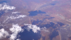 SLOW MOTION: Flying high above white clouds over the vast brown sand desert Stock Footage