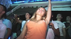 Young blonde girl in orange shirt, mini skirt dance enjoy party in nightclub - stock footage