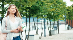 Beautiful student girl 20 years old standing in the city quay Stock Footage
