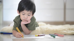 Cute Asian child drawing picture with crayon Stock Footage