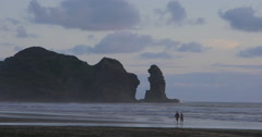 People walking on piha beach at sunset, Auckland, New Zealand Stock Footage