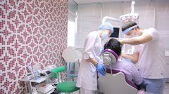 Dentist examines patient in dental office with help of nurse Stock Footage