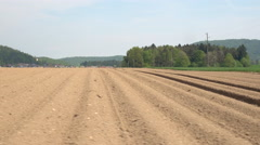 AERIAL: Empty plowed soil lines on agricultural field prepared for crop planting Stock Footage