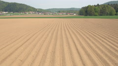 AERIAL: Empty plowed soil lines on agrarian field prepared for crop planting Stock Footage
