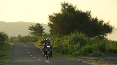 Unidentified young Indonesian guys riding scooter on empty rural road at sunrise Stock Footage