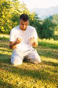 Muslim man praying outdoor at natrual environment sun beams - stock photo