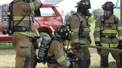 Panning view of firemen with hose outside doorway Stock Footage
