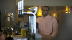 4K Friendly bartender serving & chatting with customer in city bar Stock Footage