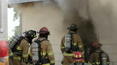 Firemen crouched outside doorway of burning house then entering smoke Stock Footage