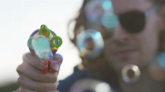 4K Handsome man in shades blows bubbles towards camera, in slow motion - stock footage
