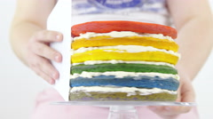 Spinning rainbow cake while removing excess cream 4K - stock footage