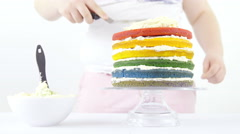 Applying cream all over rainbow cake 4K Stock Footage