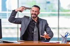 Desperate broke man committing suicide in the office - stock photo