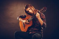 Guitarist trying out chords. - stock photo
