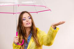 Woman in rainproof coat with umbrella. Forecasting - stock photo