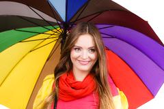 Woman in rainproof coat under umbrella - stock photo