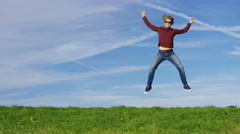 4K Happy man jumping for joy on grass, in slow motion, with space for text Stock Footage