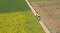 AERIAL: Tractor driving on dusty road between vast lush colourful crop fields - stock footage