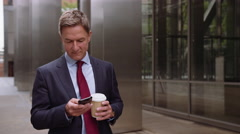 Businessman walking to work using smart phone with takeaway coffee Stock Footage