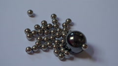 Magnet ball rolling into small metallic marbles - close up shot Stock Footage