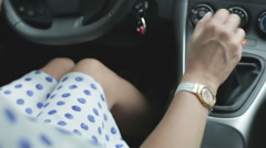 The girl in a short dress is shifting gearbox. Tanned girl's knees in a car. Stock Footage