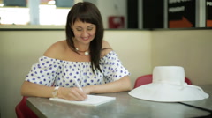 A beautiful woman writing and smiling. Stock Footage