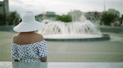 A woman sitting on a bench near a fountain. Stock Footage