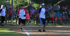 Softball game rural community hit run to first base DCI 4K Stock Footage