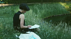 HD Pan of Young Female Painter Drawing in Park by Beautiful Pond Stock Footage