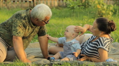 Happy family playing with a little toddler boy in an summer park with beautiful - stock footage