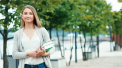 Student girl 20 years old standing in the city quay and holding her books Stock Footage