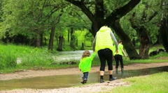 Mother With Children Walking In Puddle - stock footage