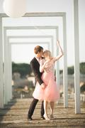 Pretty sunny outdoor portrait of young stylish couple while kissing on the roof - stock photo